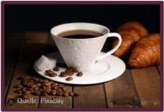 Bild mit Kaffeetasse und Kaffebohnen, im Hintergrund zwei Hörnchen