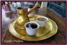 Bild mit zwei Kaffeetassen und ein Gefäß mit Holzgriff auf einem Tablett